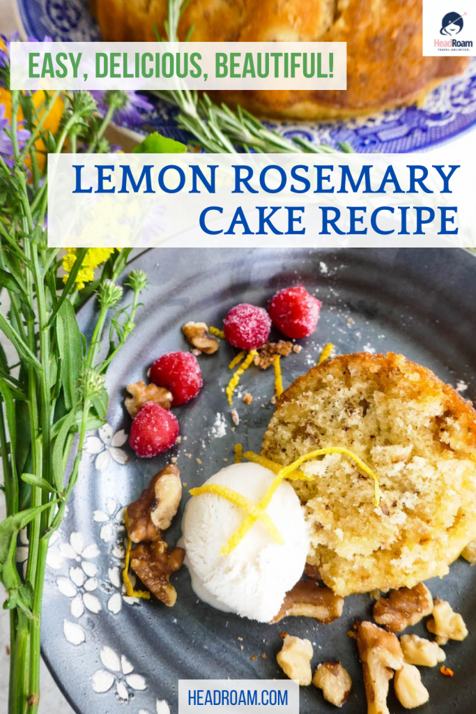 lemon rosemary cake with walnuts is shown decorated with raspberries, rosemary sprigs, lemon zest, and wildflowers