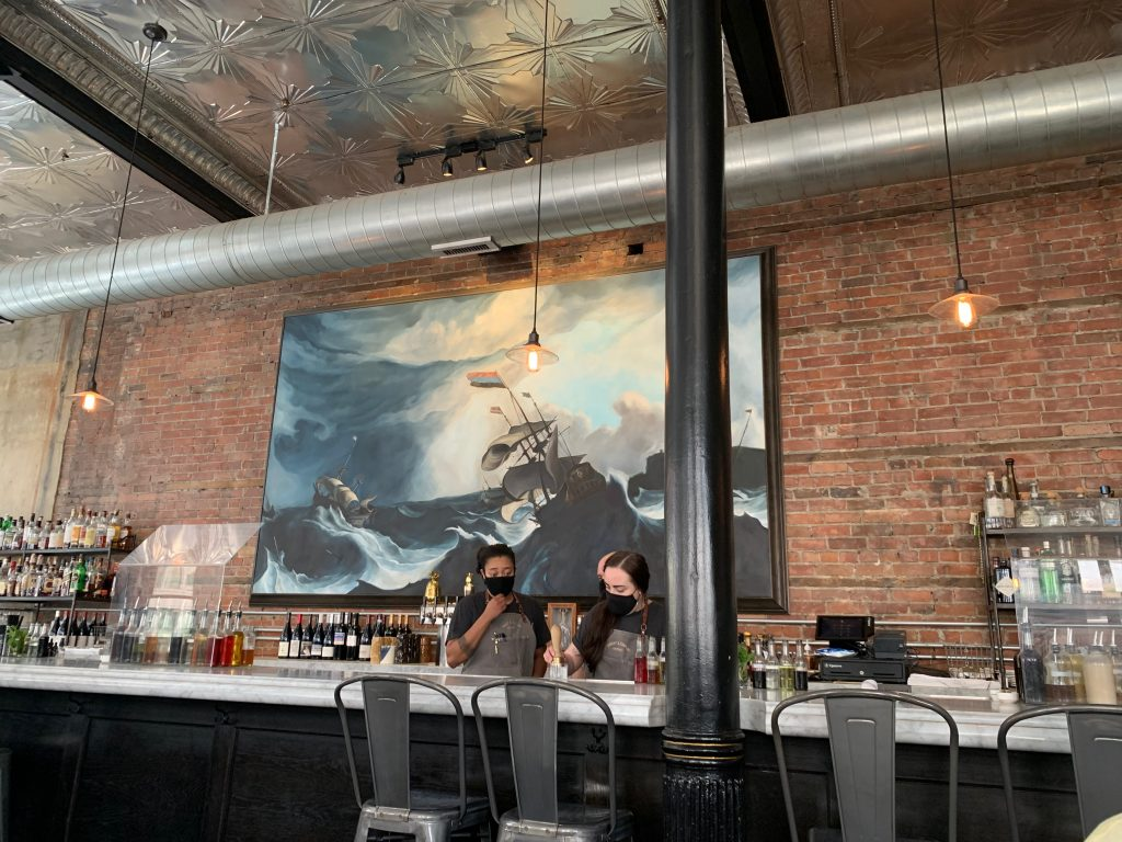 The beautiful bar at Wright and Company restaurant in Detroit features a brick wall and maritime mural.
