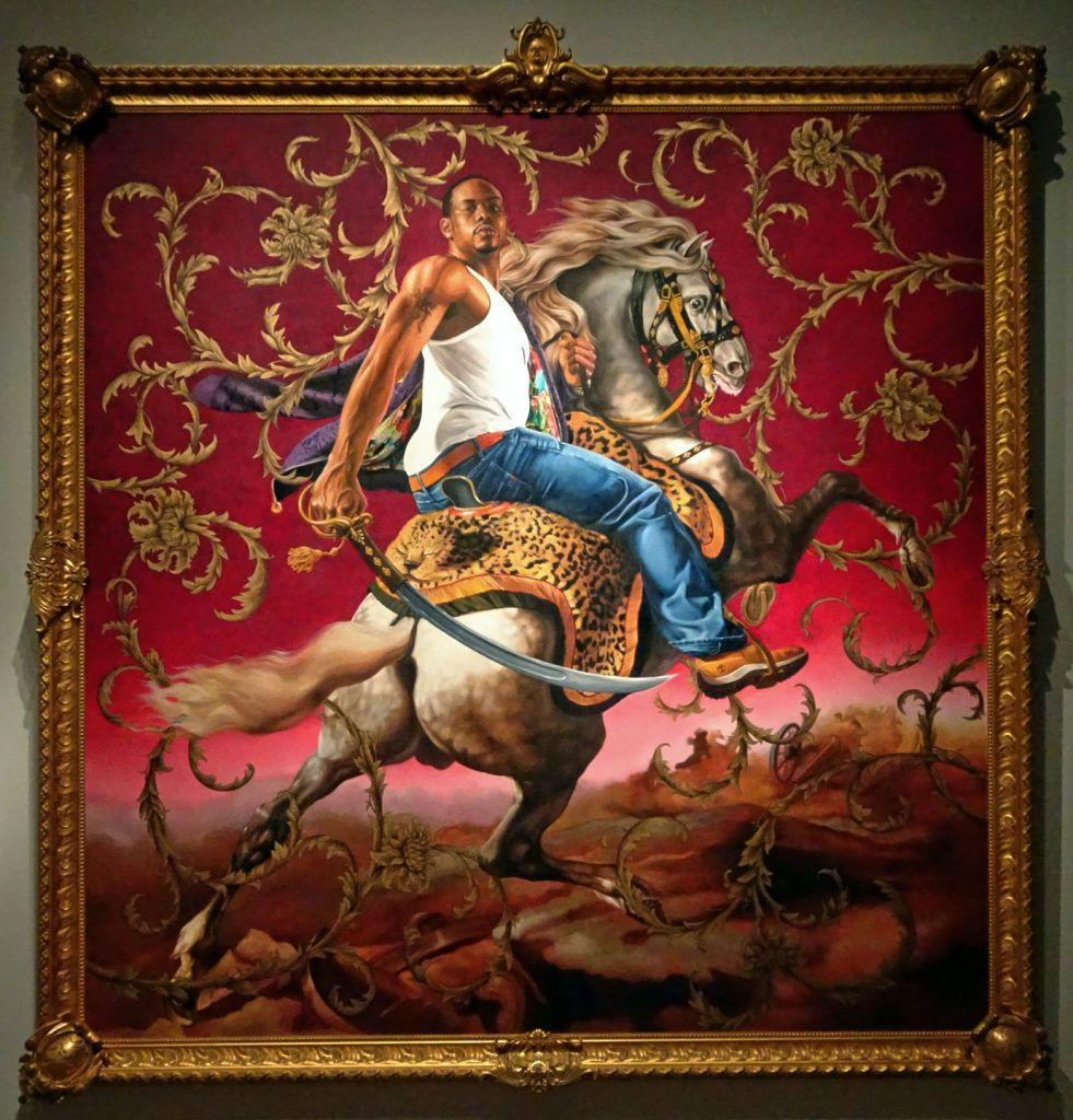 Kehinde Wiley's Hussar shows an African-American man in jeans and tank atop a fierce white horse. The man carries a saber in one hand. The background is a rich red and gold pattern.