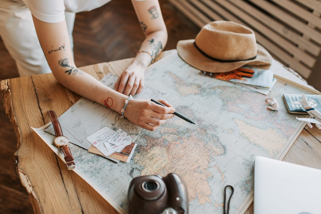 A woman with tattooed arms leans over a map to plan a trip; stock photo for destinations at Head Roam.