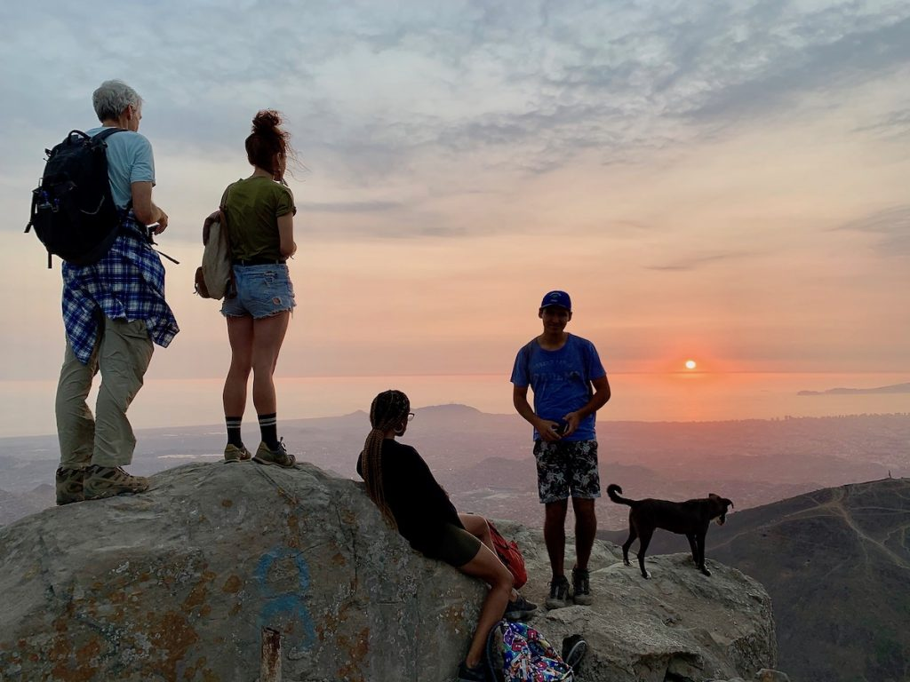 high atop a mountain rising up on the outskirts of lima 4 climbers watch a peaceful sunset