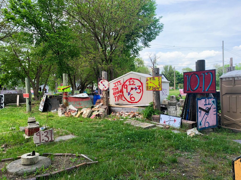 Tyree Guyton's Heidelberg Project is an open air found art extravaganza that takes over the Heidelberg block in Eastern Detroit. It's one of our favorite Fun Things to do in Detroit. This photo features different rough and colorful paintings of clocks.