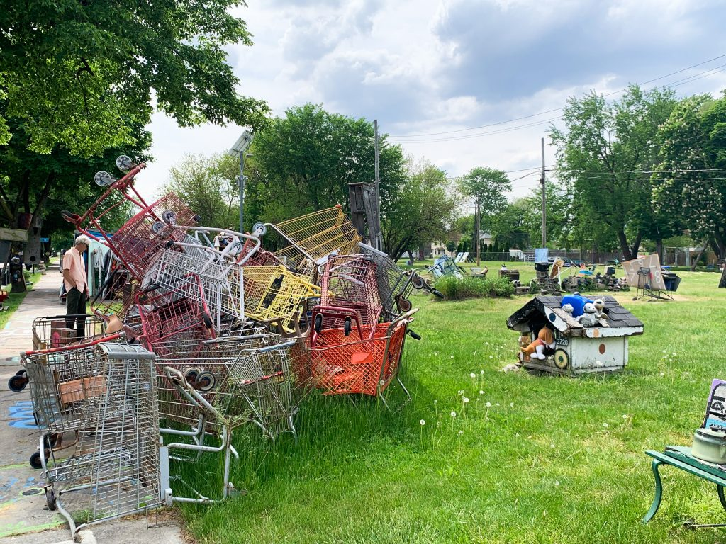 Tyree Guyton's Heidelberg Project is an open air found art extravaganza that takes over the Heidelberg block in Eastern Detroit. It's one of our favorite Fun Things to do in Detroit. In this photo, shopping carts, some in ice cream colors, pile on top of each other.