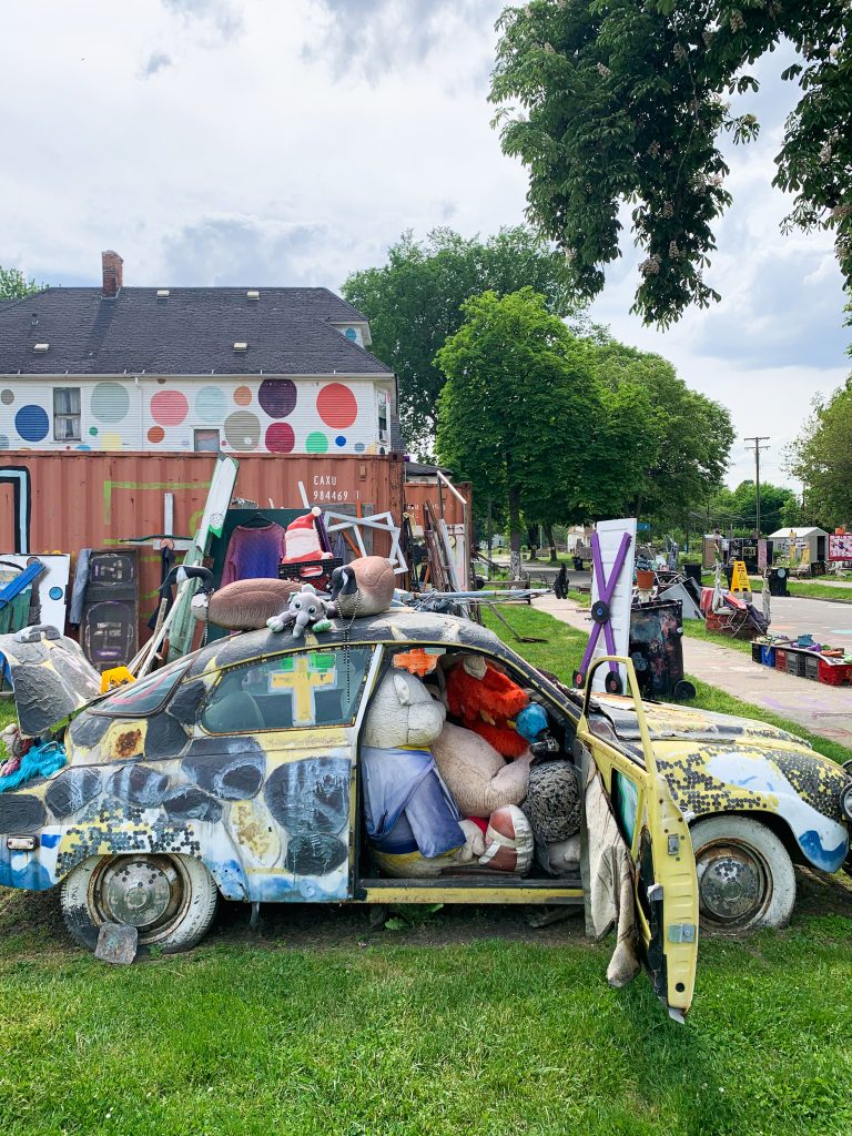 Tyree Guyton's Heidelberg Project is an open air found art extravaganza that takes over the Heidelberg block in Eastern Detroit. It's one of our favorite Fun Things to do in Detroit. This photo features a small car crammed floor to ceiling with old cushions.