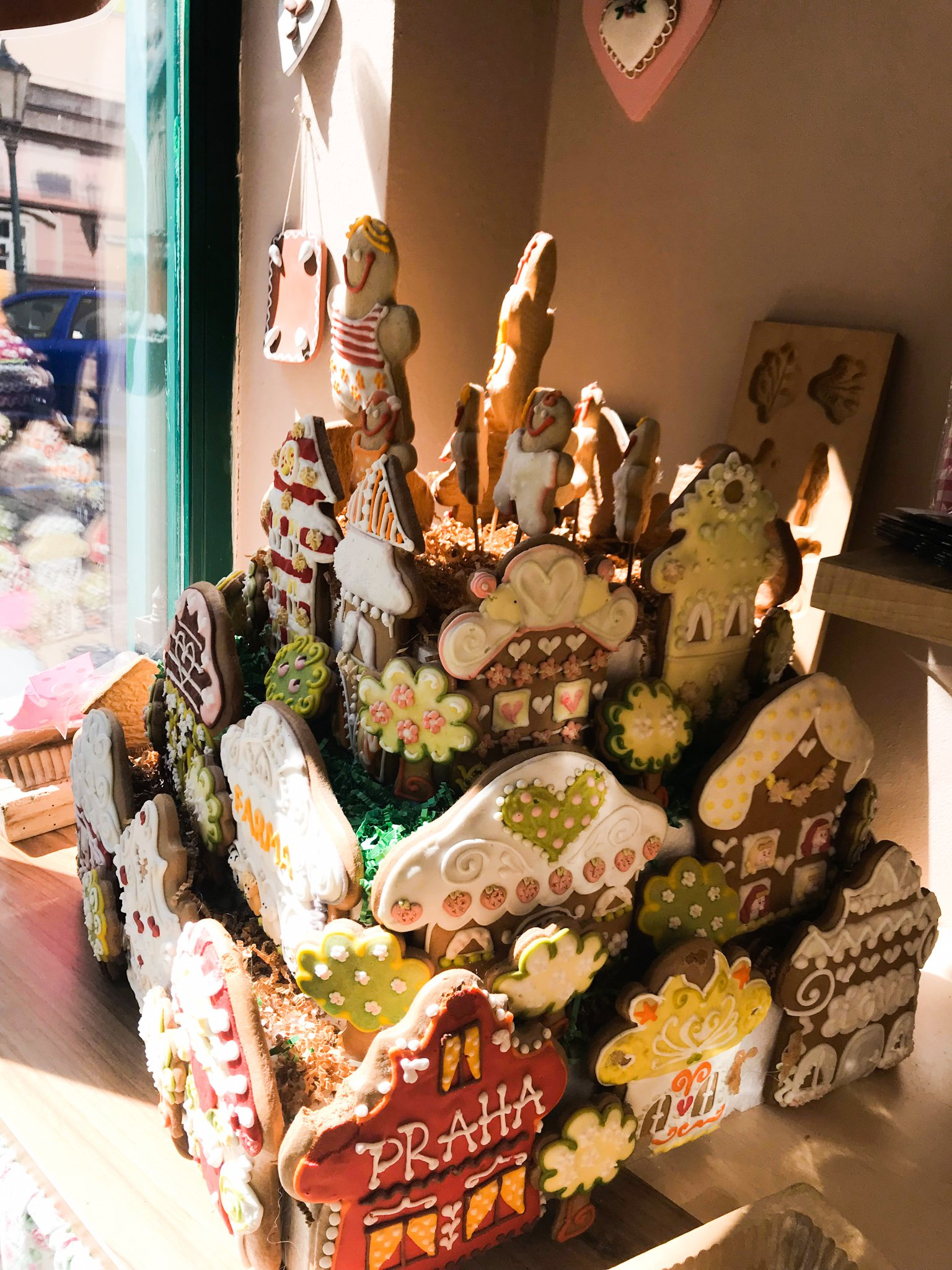 An elaborate gingerbread house in a Prague bakery features multiple levels, colorful icing, and fanciful shapes.