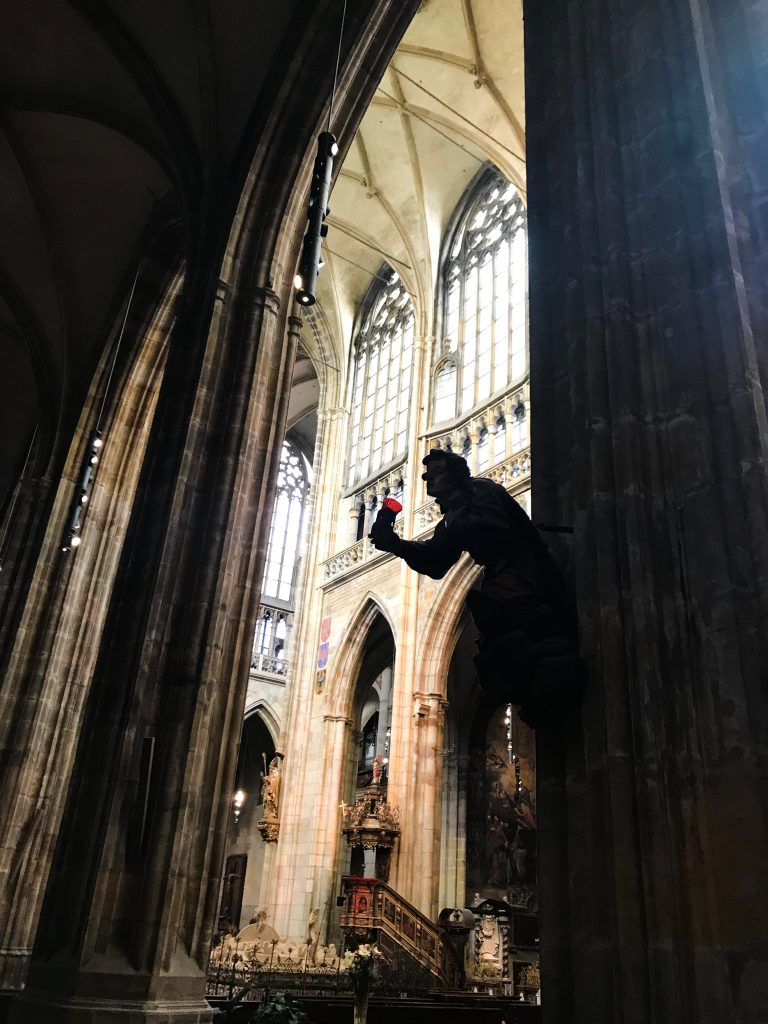 A stone figure holding a figure crops out from a pillar in St. Vitus Cathedral, Prague
