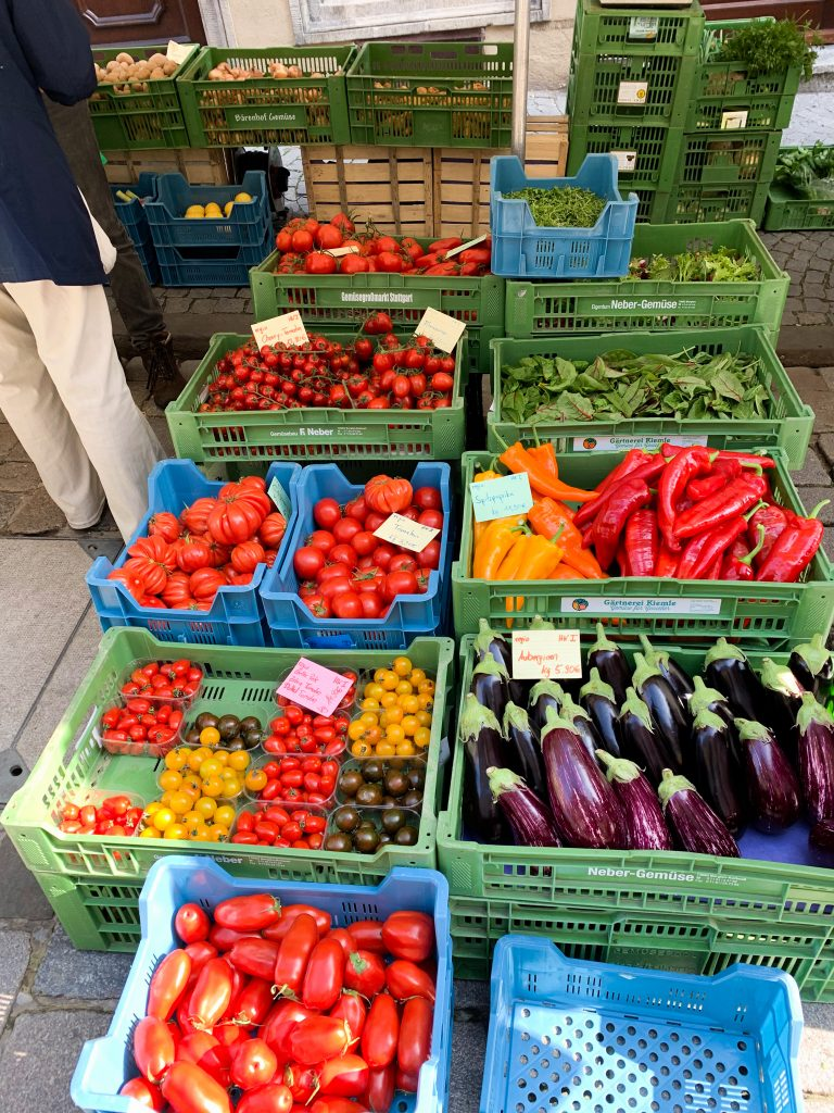 A farmers market in Germany features brilliantly colored strawberries, green beans, peppers, and eggplant.  july 2021 global cuisine
