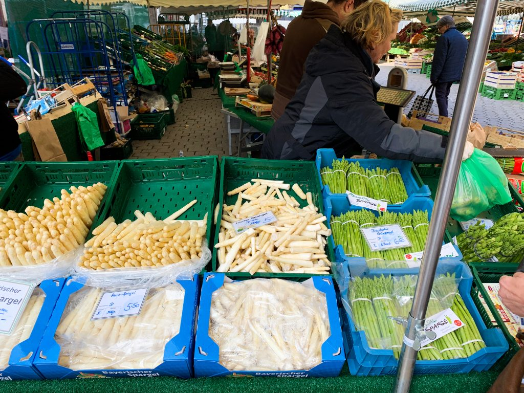 Both white and green varieties of asparagus are on display in a German farmers market. july 2021 global cuisine