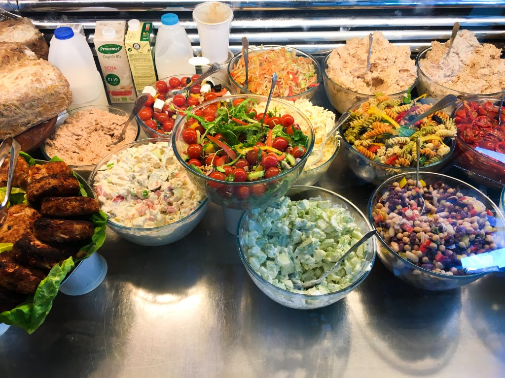 a display case at Carrington's, a wonderful Irish grocer, features cucumber salad, bean salad, tomato salad, and pasta salad, in vibrant green, red, and yellow.