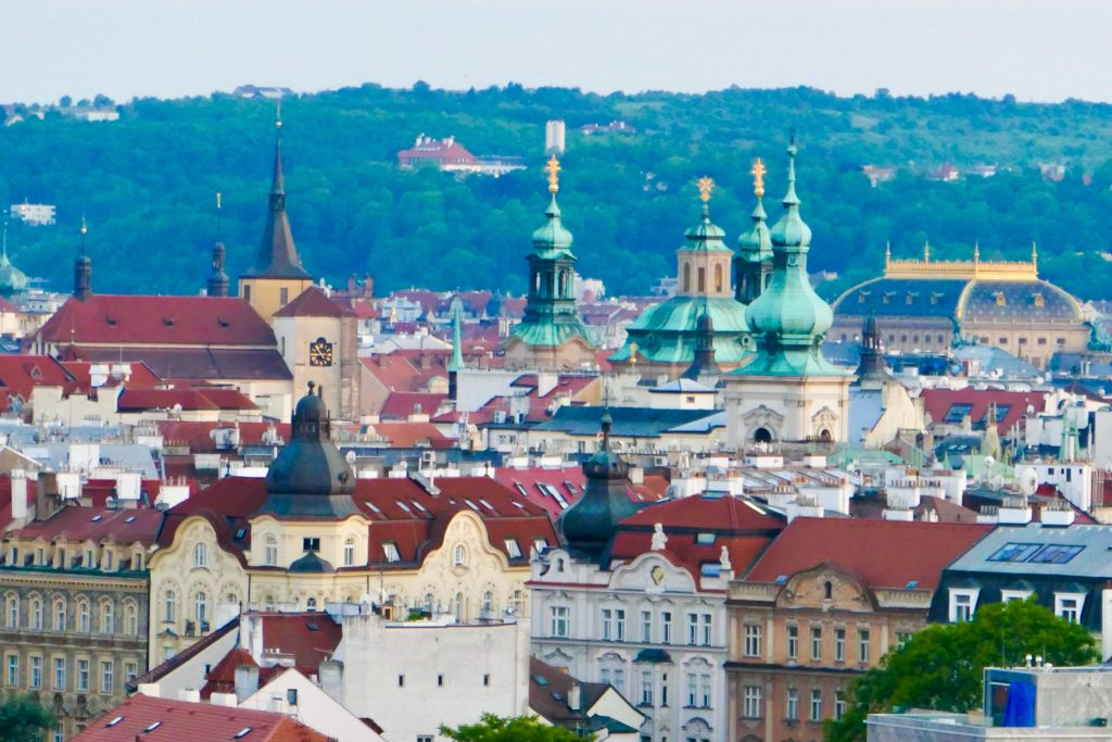 The glorious red rooftops of Prague, in the shadow of onion-topped blue copper spires: one of the reasons we recommend sightseeing Prague, Czech Republic.