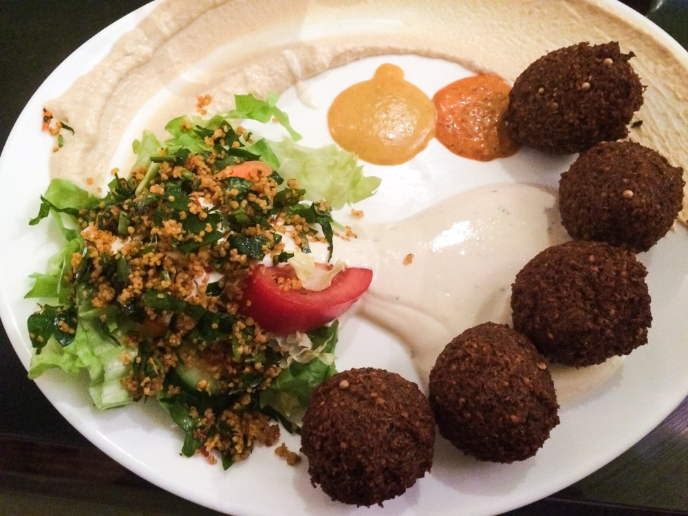 a plate of falafel from a middle eastern restaurant in Berlin's kreuzberg neighborhood features felafel patties, hummus, bright orang and yellow sauce, and a fresh bright green salad with a strip of red tomato august 2021 global cuisine