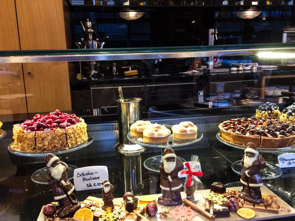 A display in a Berlin pastry shop features cheesecake topped with berries, chocolate Santas, and a bunch of other yummy stuff. august 2021 global cuisine