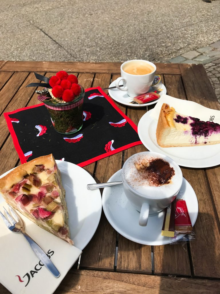 A spread of treats at a Black Forest inn: cappuccino, rhubarb cake, and cheesecake on a rustic table.  july 2021 global cuisine