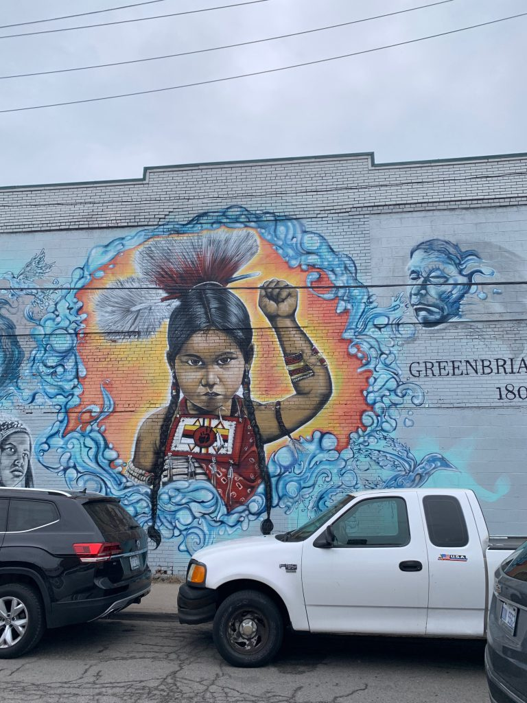 at eastern market in detroit, a native american child boldly raises her fist in a power salute in a bright turquoise and orange mural painted on a white brick wall cross-country road trip
