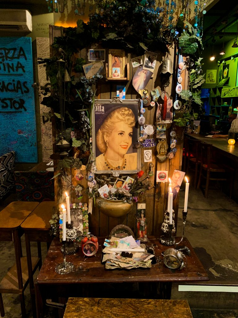immersive travel research can lead you to restaurants that you may return to more than once. For Head Roam, one was Peron! Peron! in Buenos Aires, featured in this photo, which shows a shrine to Evita, coplete with candles, medallions, buttons, and small pictures of Eva herself alongside the Virgin Mary.