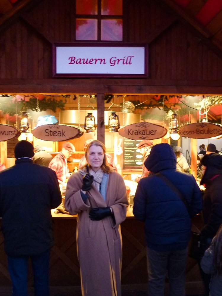 """Berlin Insider Tips: Head Roamer in Chief Nan Bauer stands beneath a """"Bauern Grill"""" sign on a food stall in a Berln Christmas market. """"Bauer"""" means """"farmer"""" in German."""