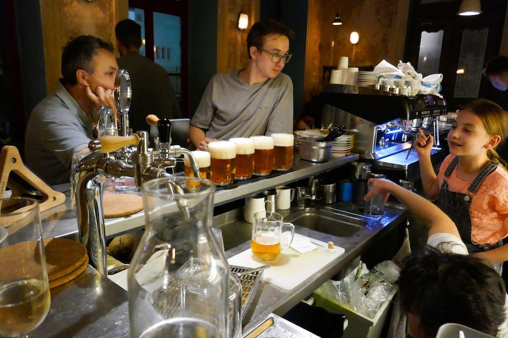 A line of pilsners on a bar in Letna, a Prague 7 neighborhood. In the dark bar, customers look at the line of beer.