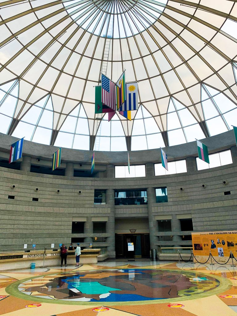 The entry to the Charles H. Wright Museum of African American History features a floor with a large, multi-color graphic mosaic and a glass paneled dome overhead.
