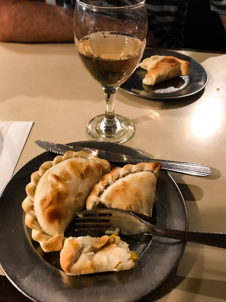 a plate of empanadas, perfectly browned with crimped edges, makes a great dinner alongside a glass of wine in Buenos Aires august 2021 global cuisine
