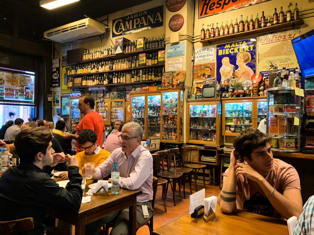 august 2021 destinations a colorful bar in Buenos Aires features wooden tables and rows of local beer bottles on the walls along with vintage posters
