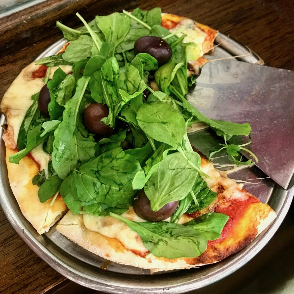 a Buenos Aires pizza features crisp crust, tomato sauce, olives, and a topping of fresh arugula august 2021 global cuisine