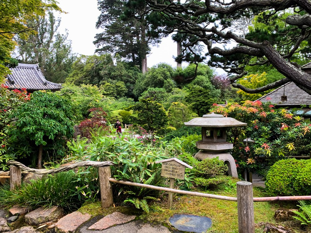 august 2021 destinations a pathway landscaped with Japanese plants and featuring a small stone temple in the Japanese Garden in San Francisco's Golden Gate park