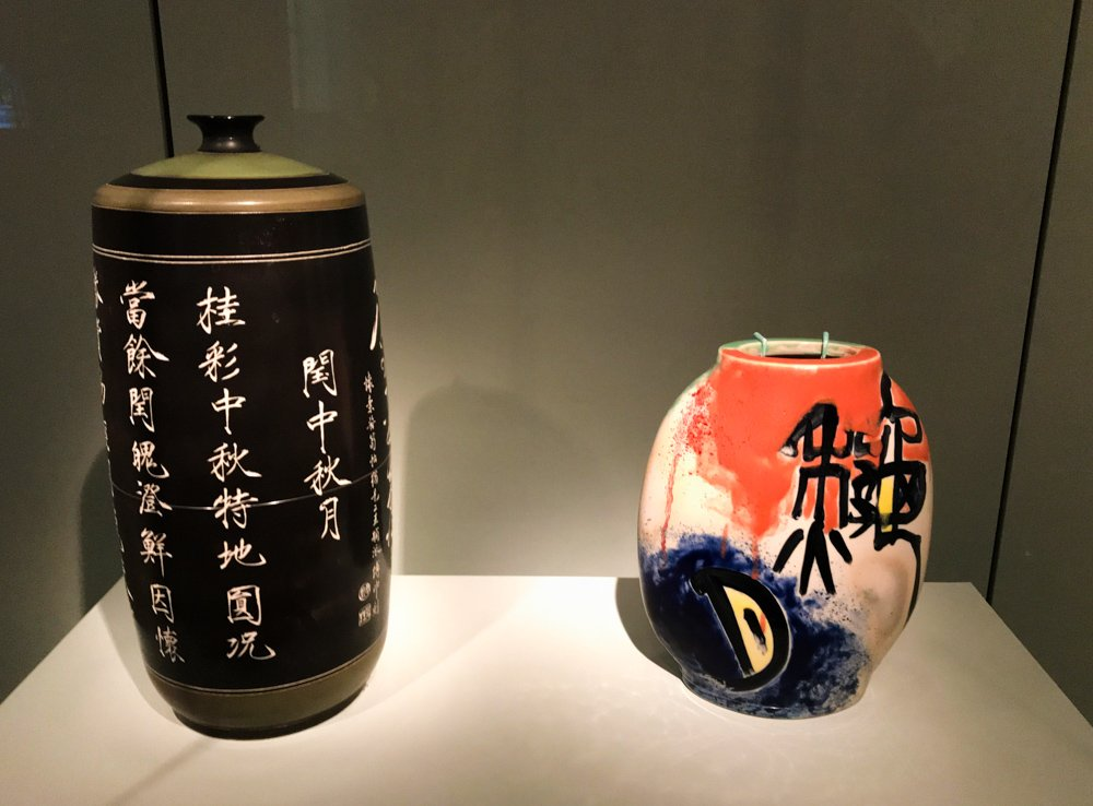 2 vases by contemporary artist Fu Shen, one black with gold calligraphy, the other featuring abstract splashed of bright orange and black with stylized chrysanthemums from the Asian Art Museum in San Francisco