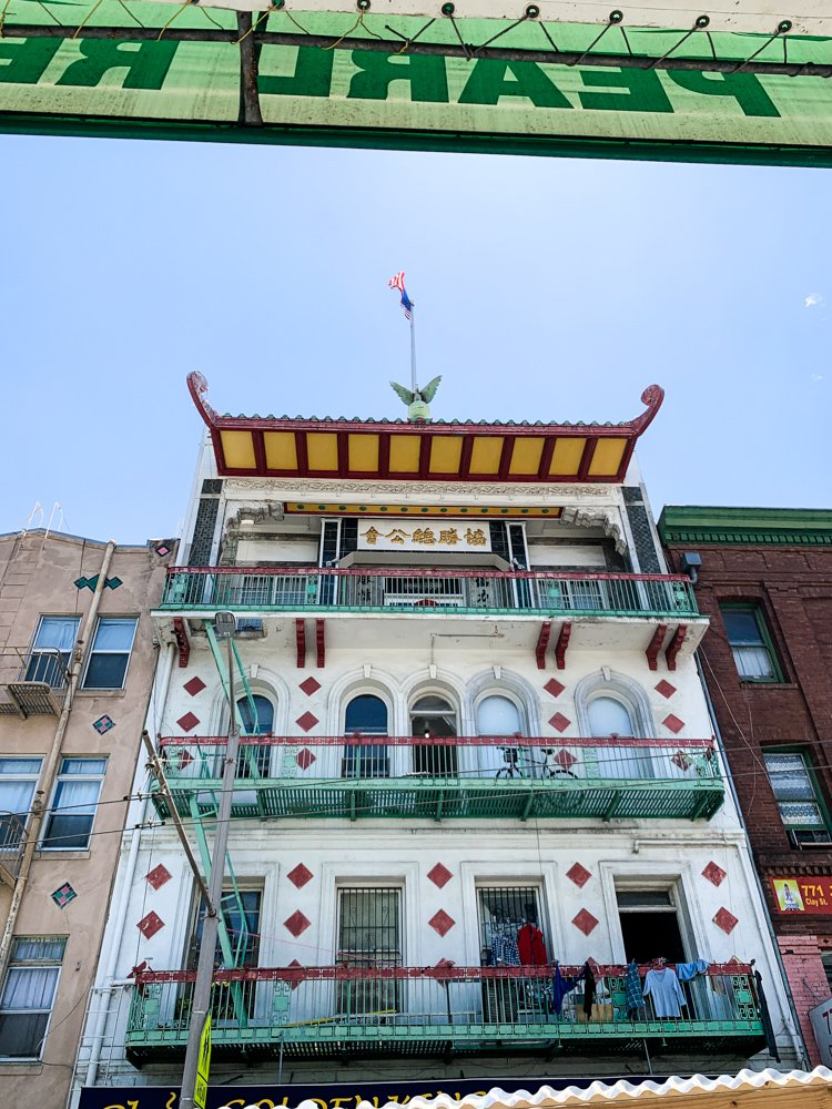 An apartment building in Chinatown features a white facade with brilliant turquoise and red decorations