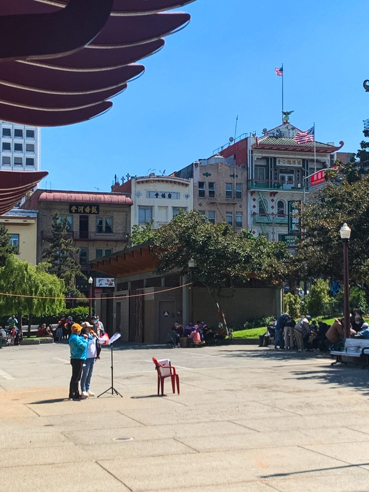 a couple performs karoake to an empty St. Mary's Square in San Francisco's Chinatown.