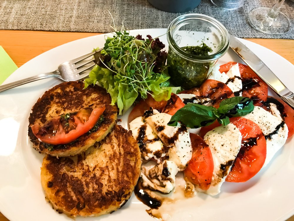 Golden brown German potato pancakes are served next to a Caprese salad, with a small pot of pesto and a mound of fresh greens. august 2021 global cuisine from head roam