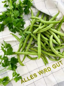 a pile of fresh greens beans sits on top of a pristine kitchen towel inscribed with All Is Good in German