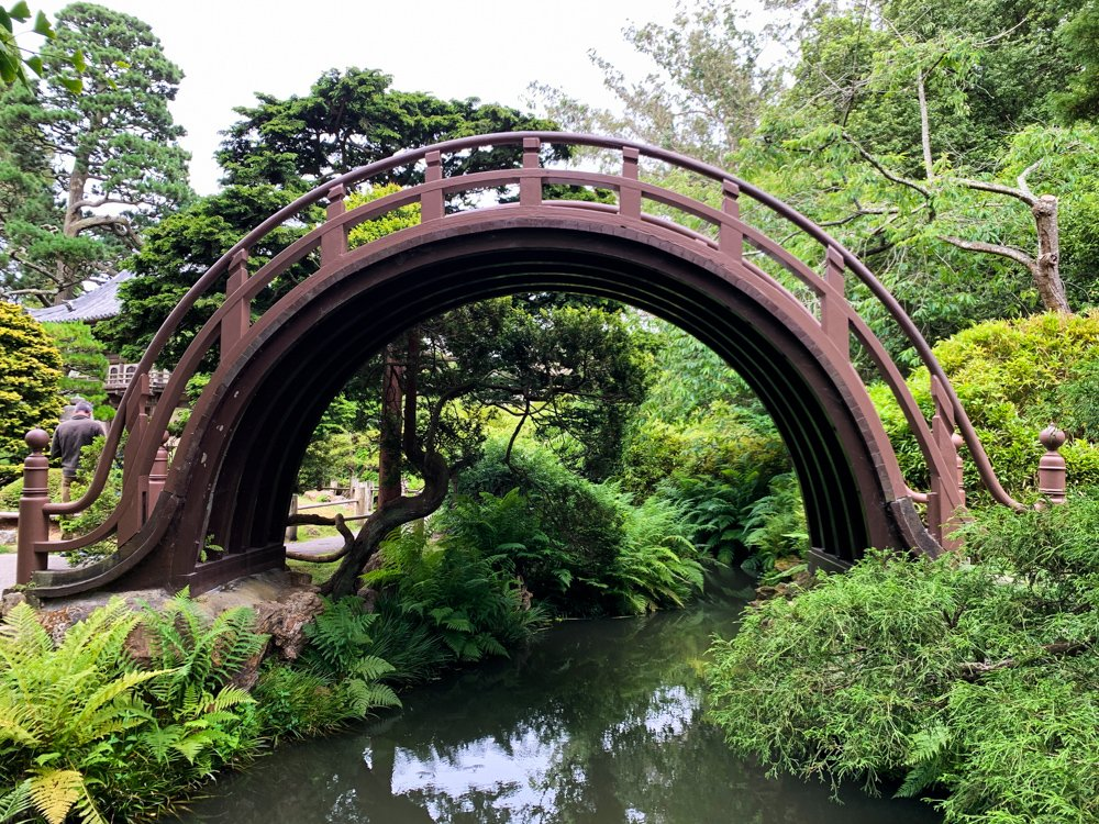 a perfect half circle in a rust colored metal arcs like a rainbow over a pond in the Japanese Garden in Golden Gate park in San Francisco