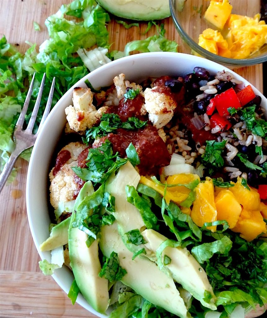 a vegetarian mole bowl brims with fresh cauliflower, mango, avocado and herbs, and features rice, beans, and a mole sauce