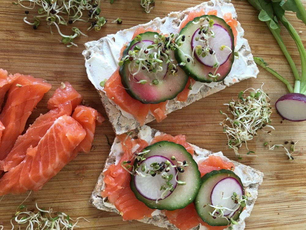 Homemade gravlax on Wasa crispbread is thinly sliced and served over a rich cream cheese, topped with thin crunchy slices of cucumber, radishes, and a sprinkling of sprouts. august 2021 global cuisine