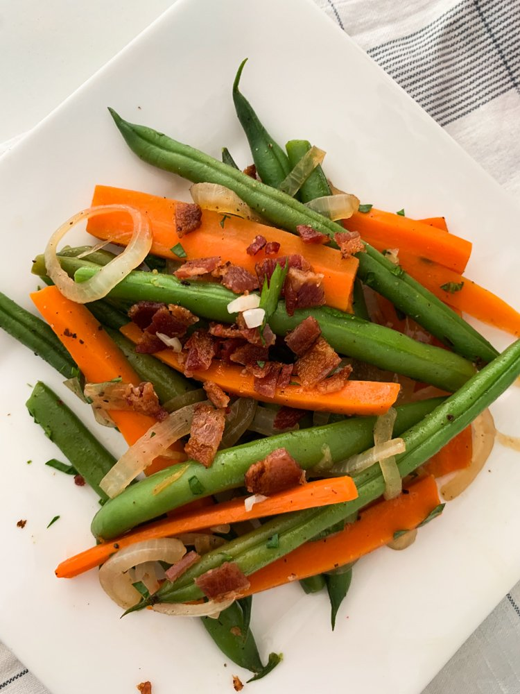 a plate of bright green beans, bright orange carrots, and sauteed onions are sprinkled with bacon crumbles august 2021 global cuisine