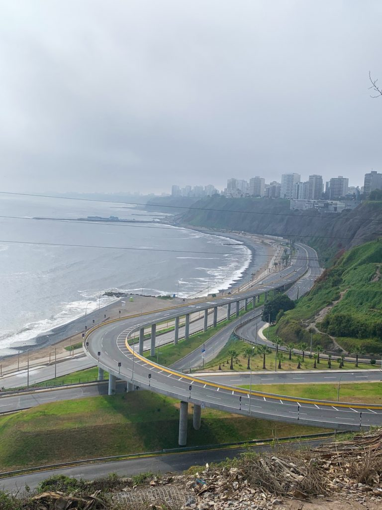 responsible tourism includes caring for the environment, brought home to the author by this photo of the completely empty Malecon, or ocean drive along Lima's curving coastline, in Peru during spring of 2020, when traffic vanished.