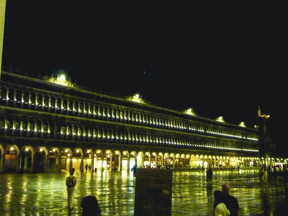 To illustrate rethinking travel as part of responsible tourism, a photo shows a night in St. Mark's Square in Venice after rain, the bright lights of the arcade reflected in the wet pavement below. The photo was taken in 2015, when the city was already feeling the effects of over-tourism.